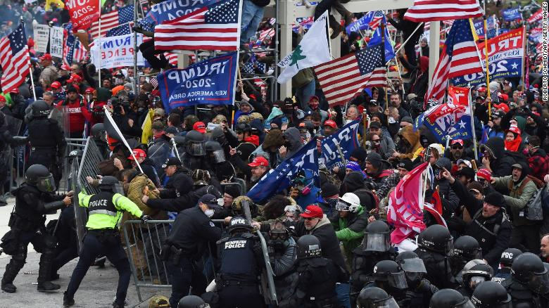 TOPSHOT - Trump supporters clash with police and security forces as they push barricades to storm the US Capitol in Washington D.C on January 6, 2021. - Demonstrators breeched security and entered the Capitol as Congress debated the a 2020 presidential election Electoral Vote Certification. (Photo by ROBERTO SCHMIDT / AFP) (Photo by ROBERTO SCHMIDT/AFP via Getty Images)